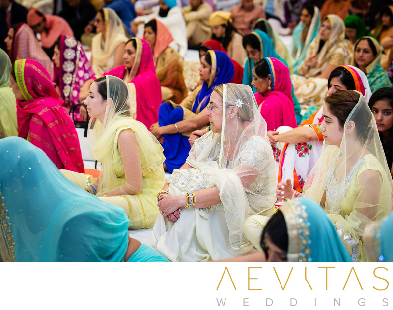Women in colorful veils at Indian wedding ceremony