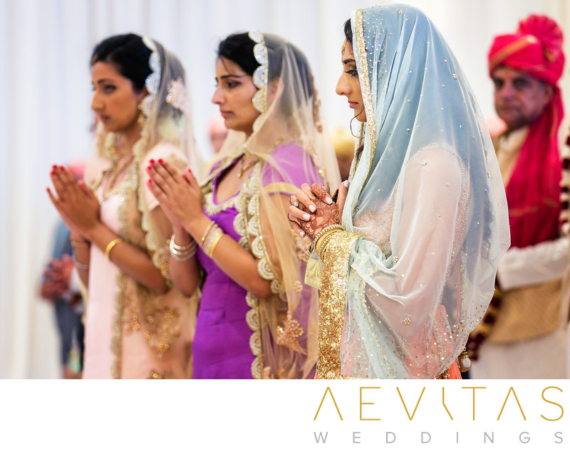 Women hold hands in prayer at Indian wedding ceremony