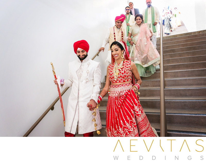 Couple and family walking down stairs at Indian wedding