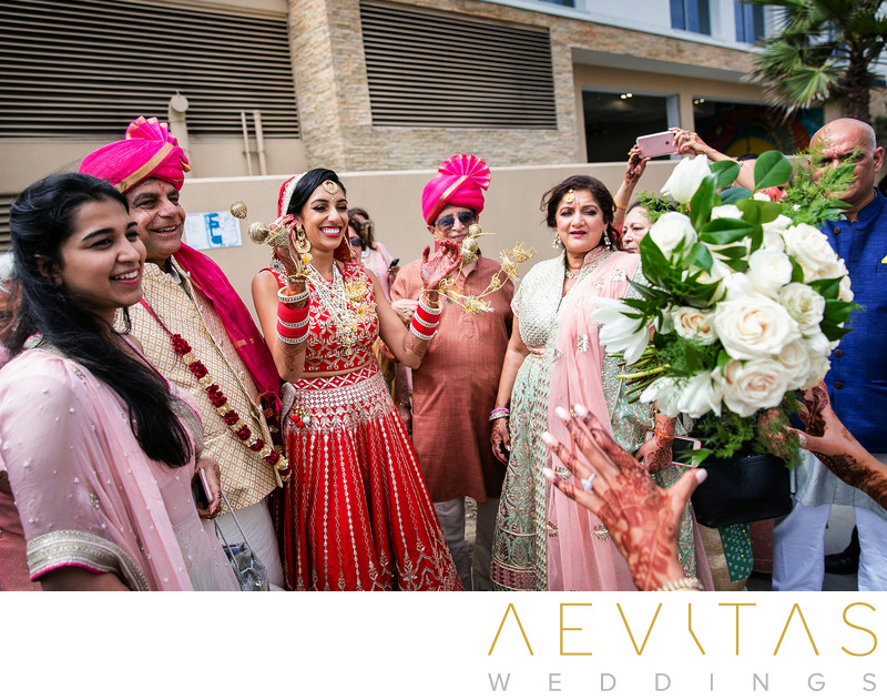 Action shot of bride throwing bouquet at Indian wedding