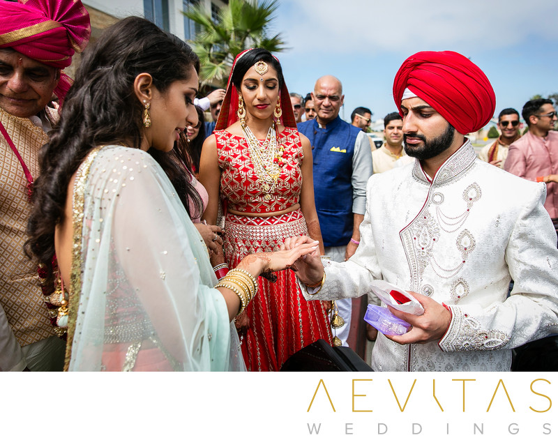 Groom giving ring to bride's sister at Indian wedding