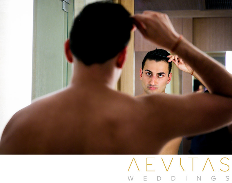 Groom brushing hair in suite mirror at Pasea Hotel