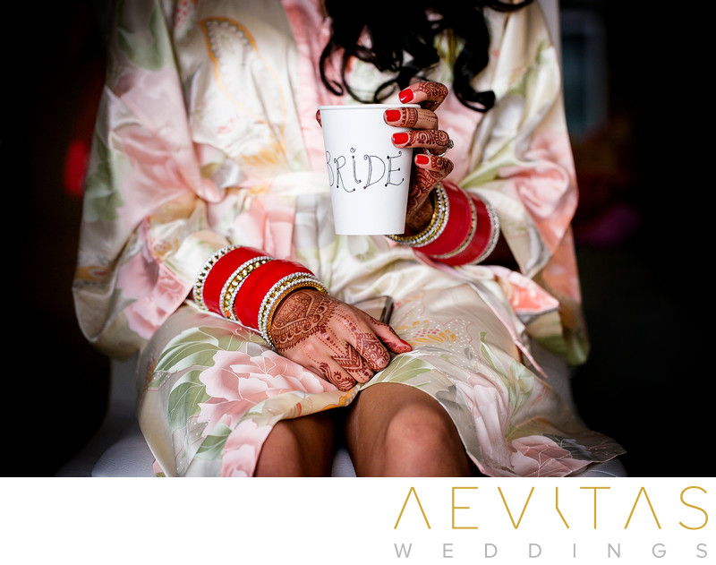 Bride drinking coffee in suite at Indian wedding