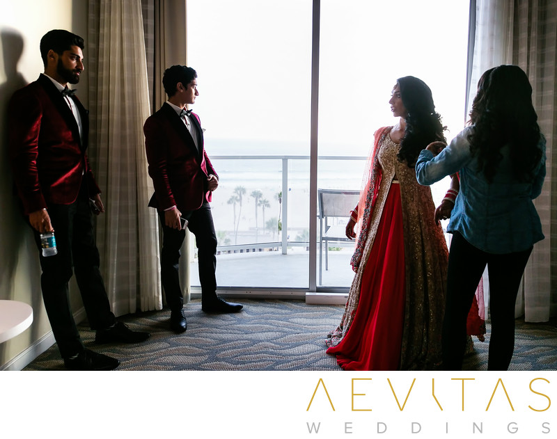 Casual bride getting ready with brothers in hotel suite
