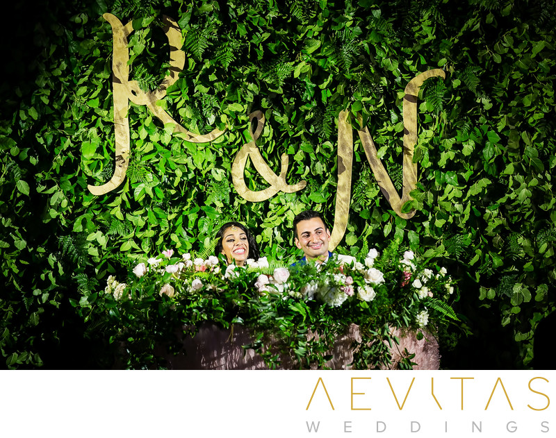 Couple at sweetheart table with lush greenery