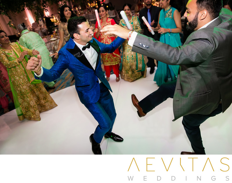Groom dancing with friend at Indian wedding reception