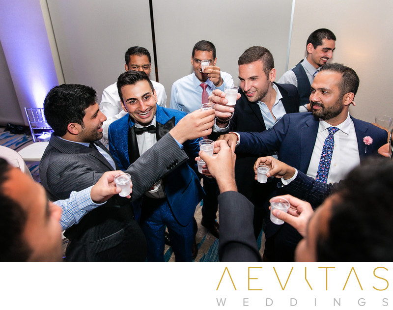 Groom and friends doing shots at Pasea Hotel wedding
