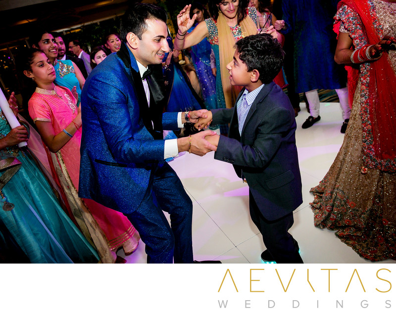 Groom and young boy dancing at Indian wedding reception