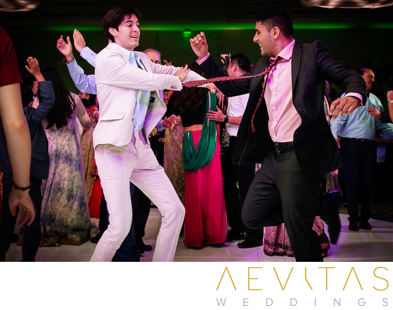 Two men dancing at Indian wedding reception