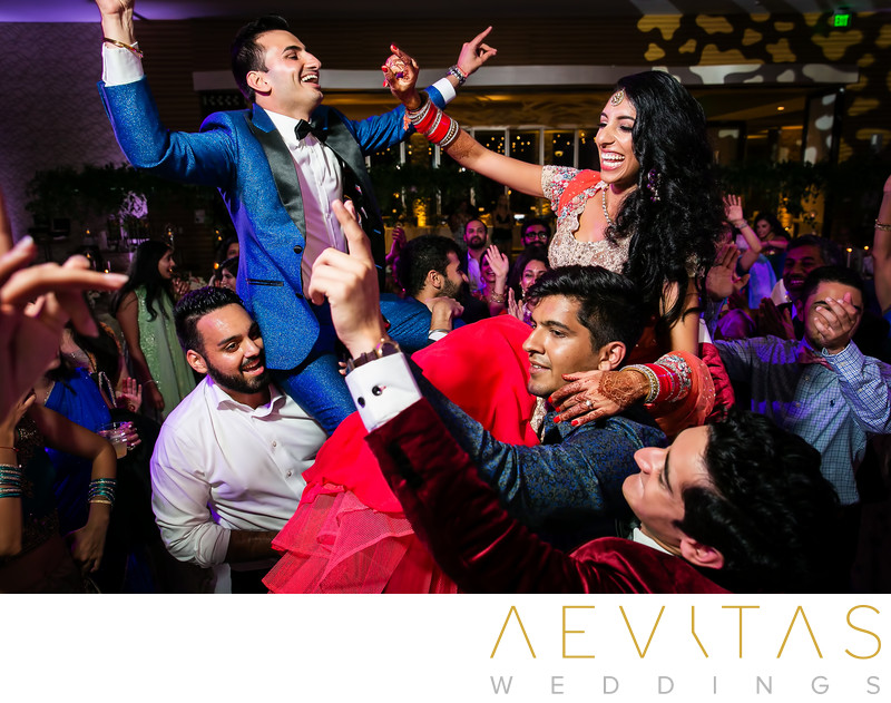Bride and groom on shoulders at Indian reception