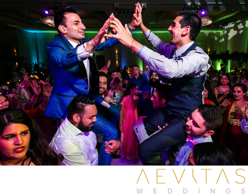 Groom and brother on shoulders at Indian wedding