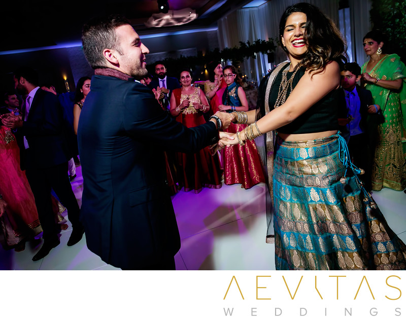Man and woman spin on dance floor at Indian wedding