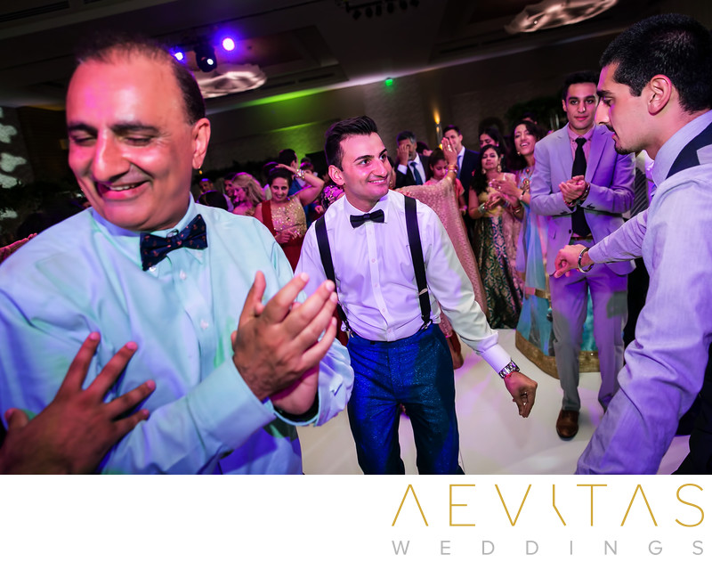 Candid groom dancing with father at Indian wedding