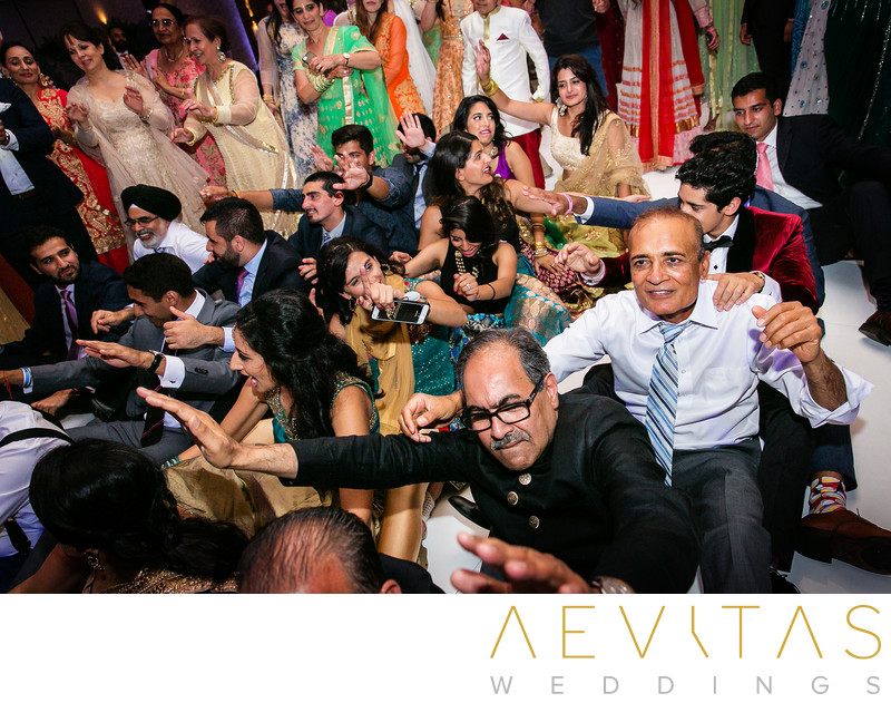 Wedding guests seated on one another at Indian party