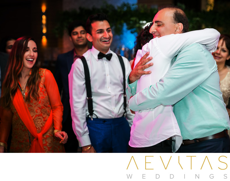 Brother embraces father at Indian wedding reception