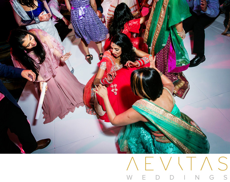 Bride getting down with friend at Indian wedding party