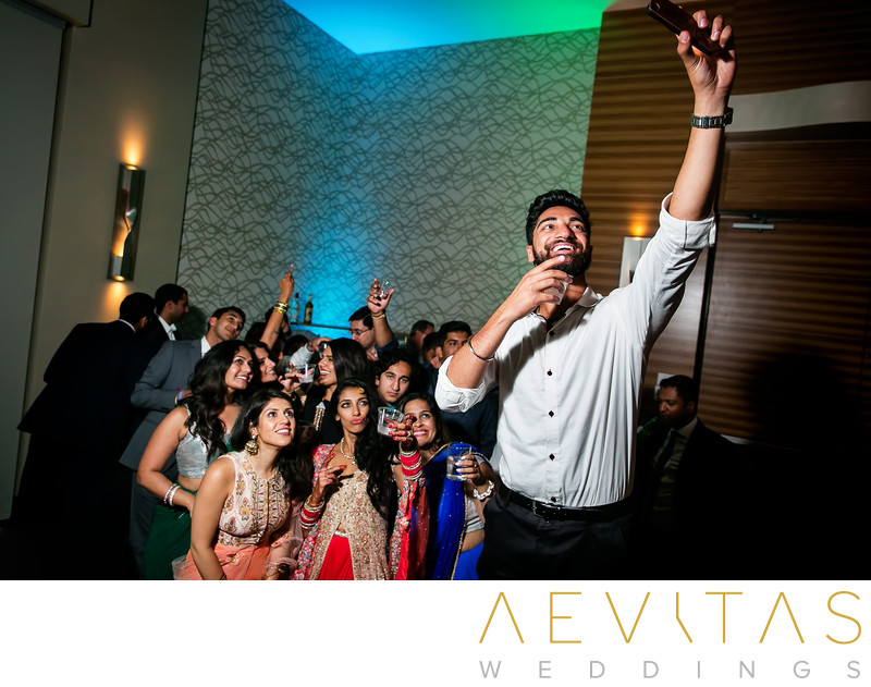 Brother taking selfie at Indian wedding reception