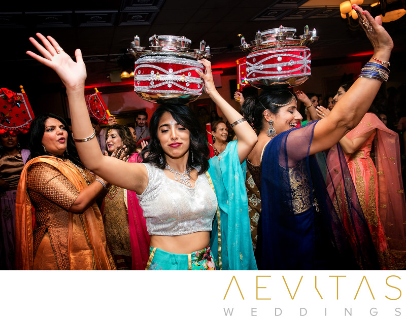 Women with red drums on head at Indian wedding party