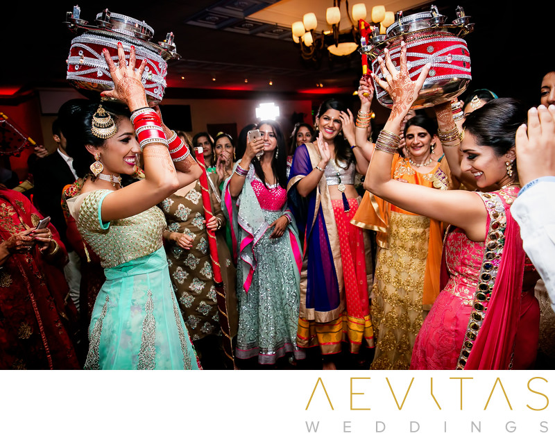 Bride dancing with drum on head at Indian Sangeet party