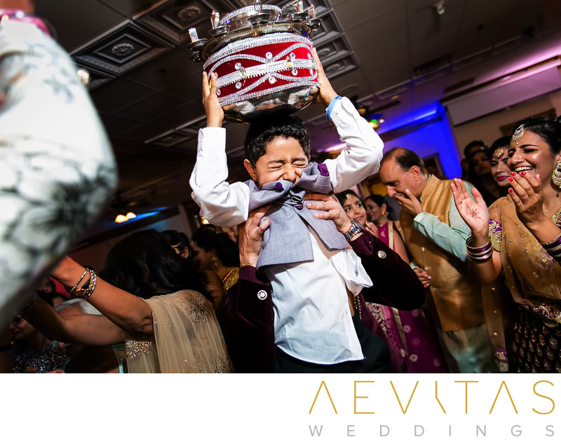 Young boy with drum on dance floor at Indian wedding