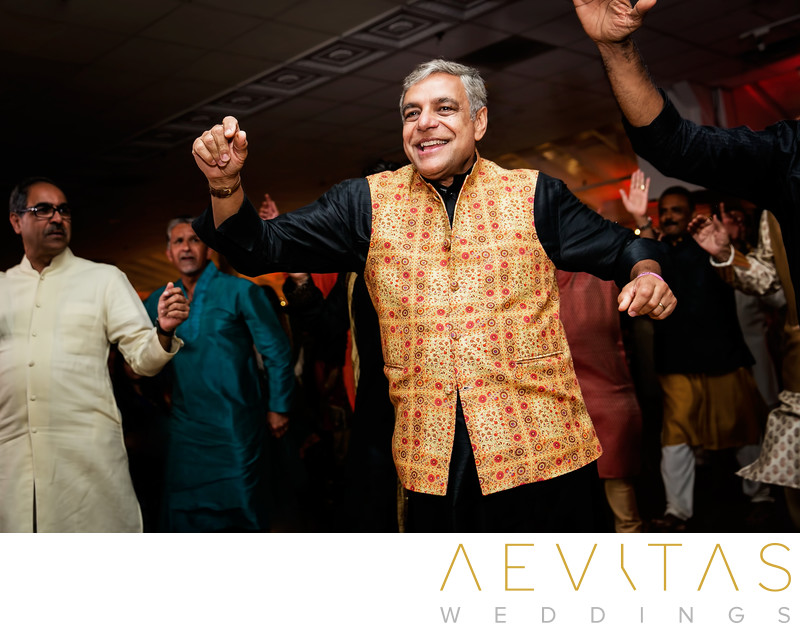 Action shot of father dancing at Indian wedding party