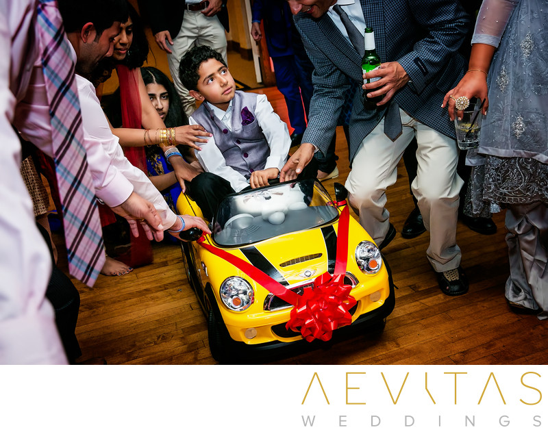 Young boy on car at Indian wedding party
