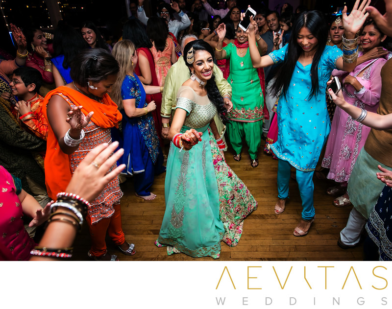 Bride dancing surrounded by friends at Indian wedding