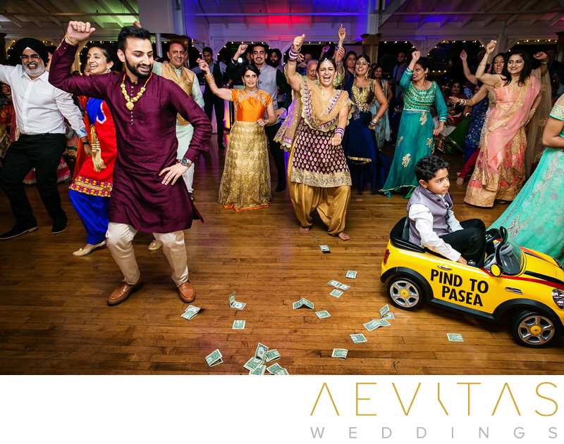 Wedding guests dancing with boy in yellow toy car