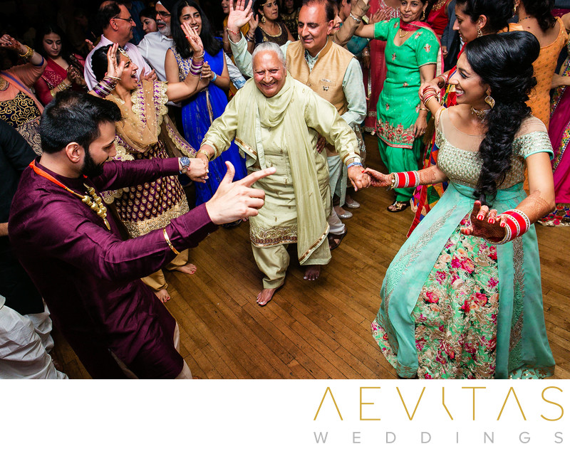 Grandma dancing with couple at Indian wedding party