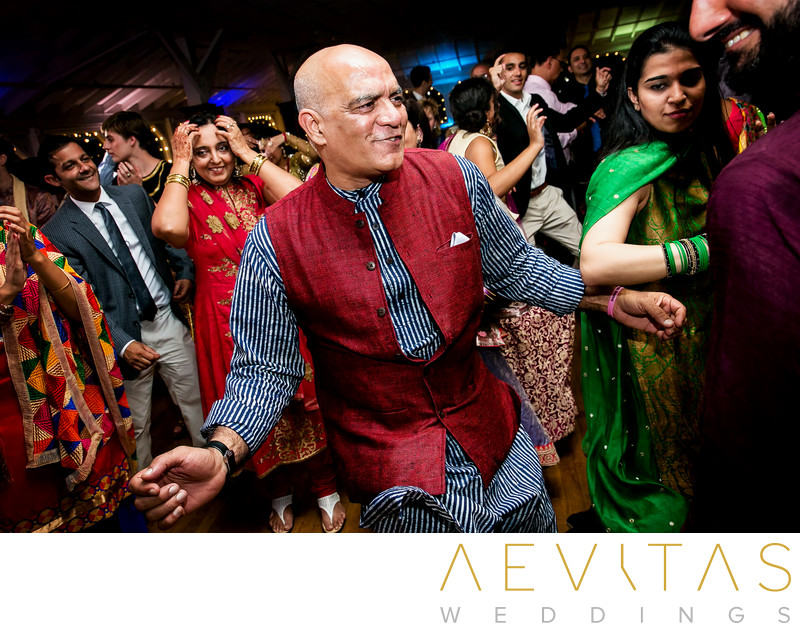 Man in red waistcoat dancing at Indian Sangeet