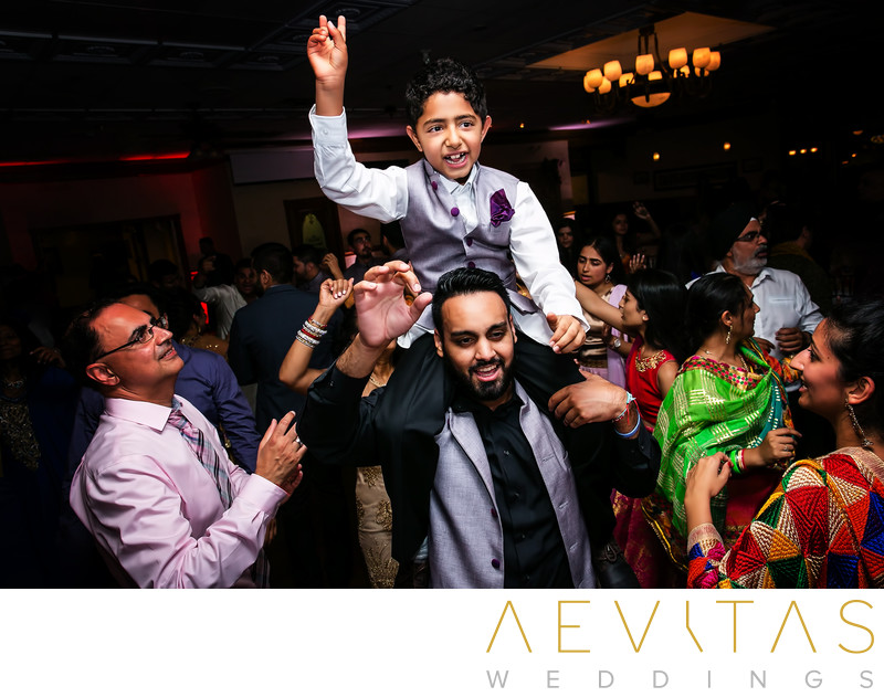 Young boy on shoulders at Indian Sangeet party