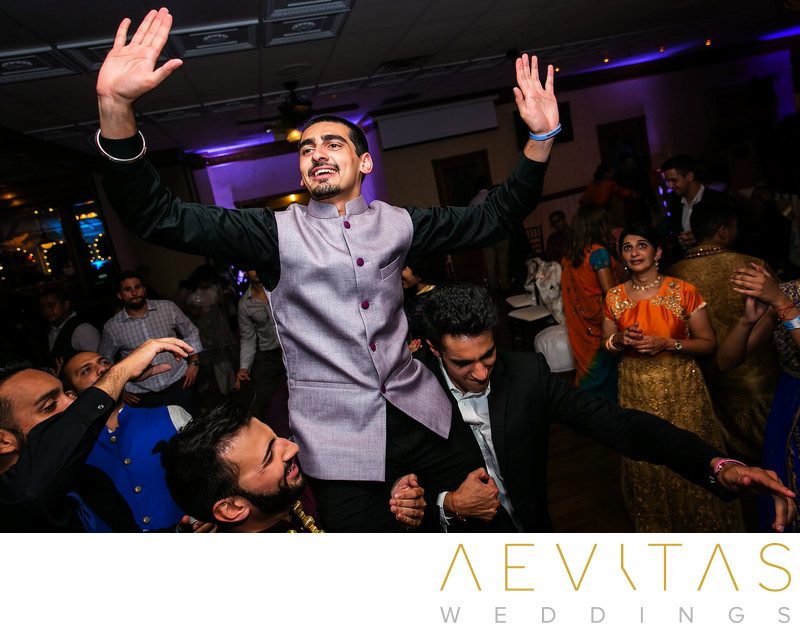 Groomsman on shoulders at Indian wedding party