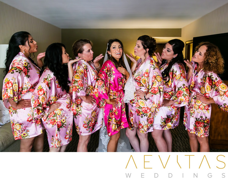Bride with bridesmaids blowing kiss in floral gowns
