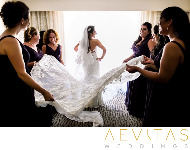 Bridesmaids fluffing bride's wedding dress in suite