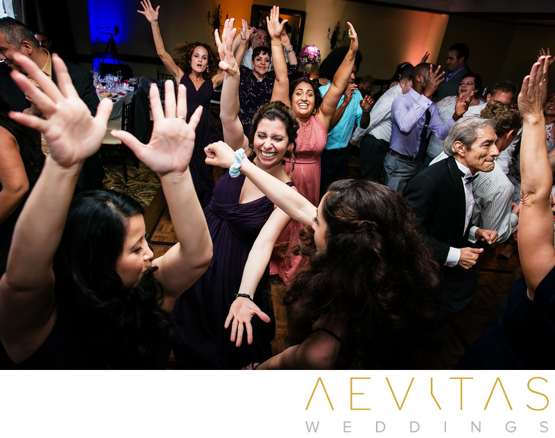 Wedding guests with hands in the air on dance floor