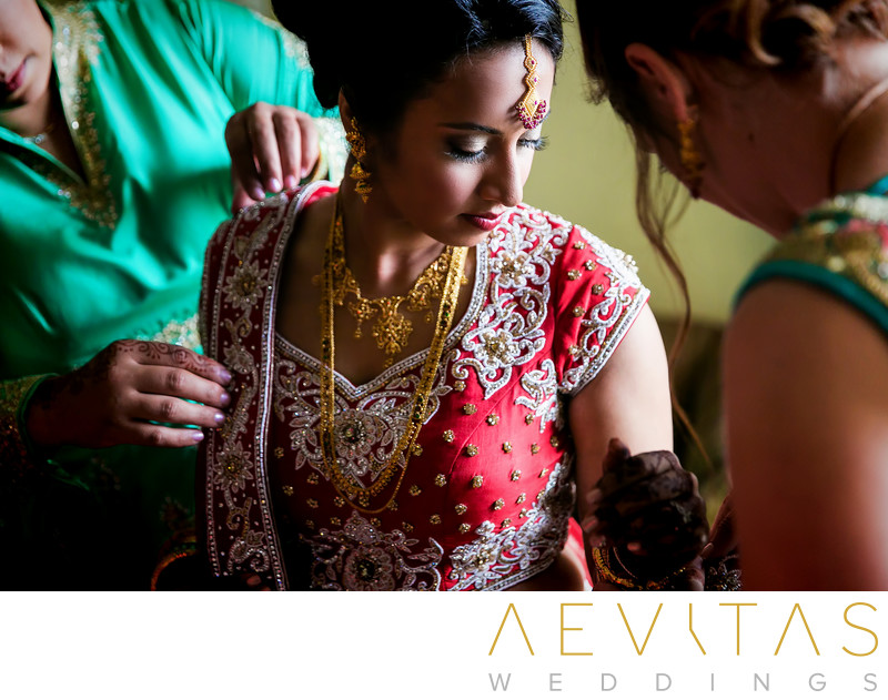 Bride getting ready in red sari at Bahia Resort Hotel