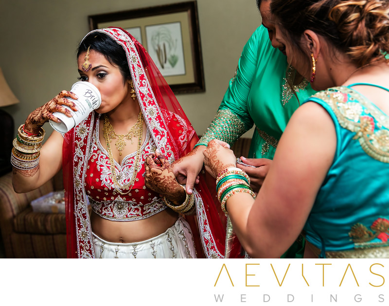 Indian bride drinking coffee in red sari in San Diego