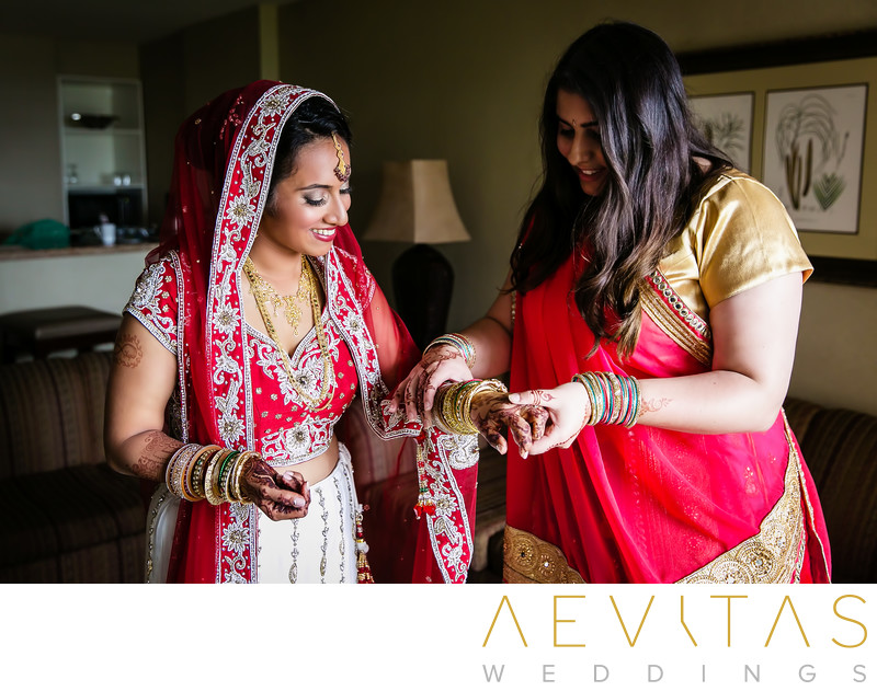 Indian bride putting on bangles with bridesmaid