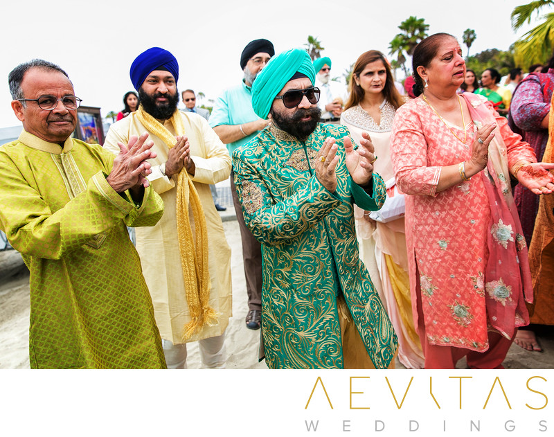 Wedding guests clapping at beach Baraat in San Diego