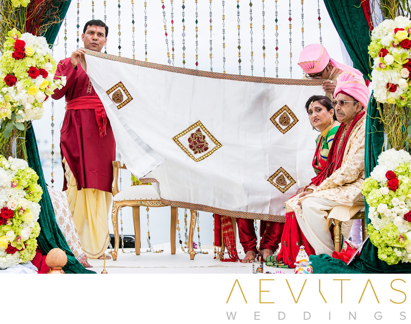 Officiant holds cloth at Indian wedding ceremony