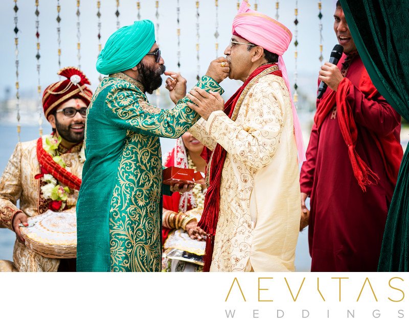 Fathers feed one another sweets at Indian wedding