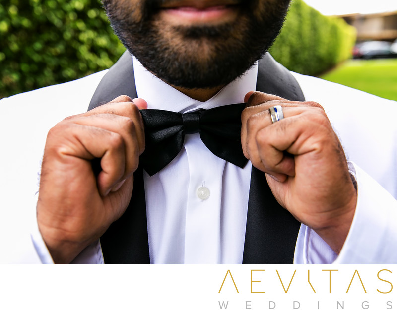 Close-up photo of groom adjusting bow tie in San Diego