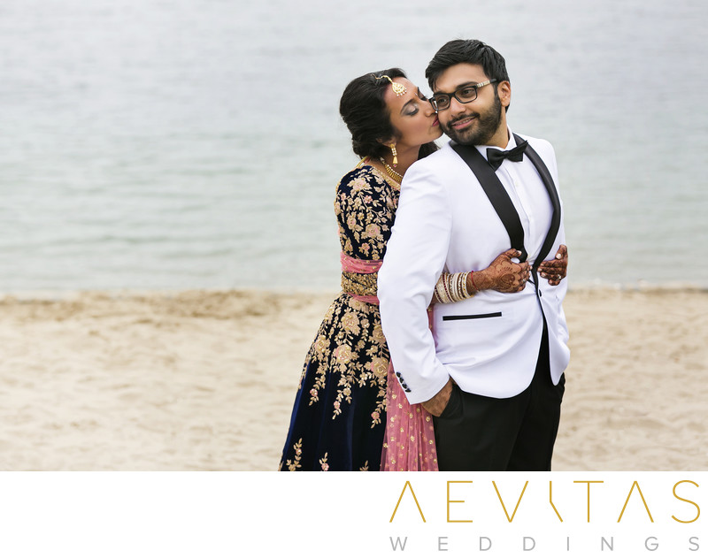 Bride kisses groom on beach at Bahia Resort Hotel
