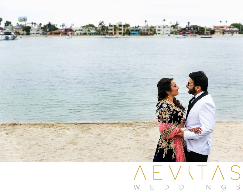 Couple embrace on beach at Bahia Resort Hotel San Diego