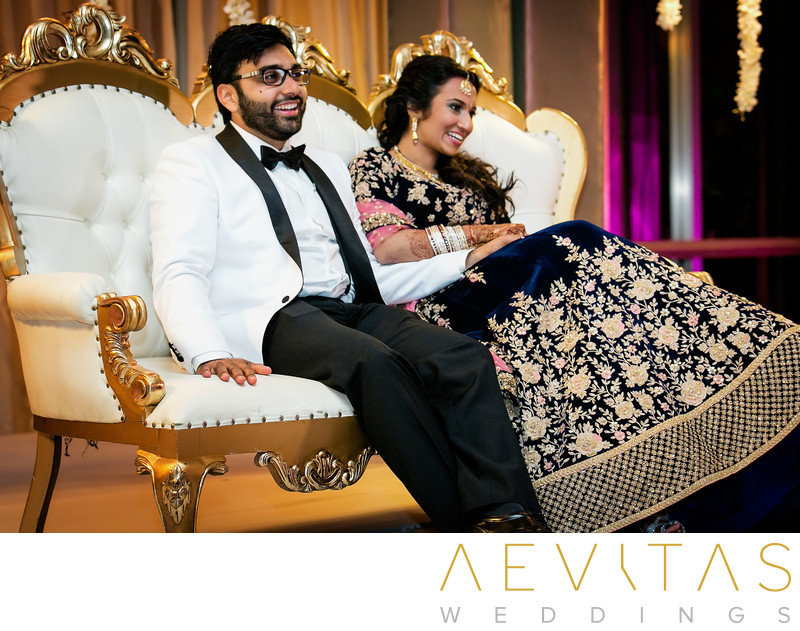 Bride and groom on white and gold ornate chaise lounge