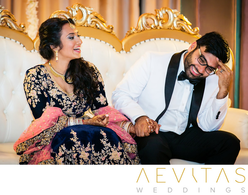 Bride and groom laughing on white and gold sofa