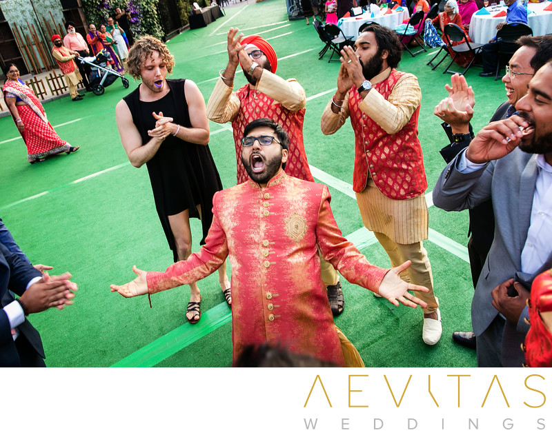 Action shot of groom dancing at Indian Baraat