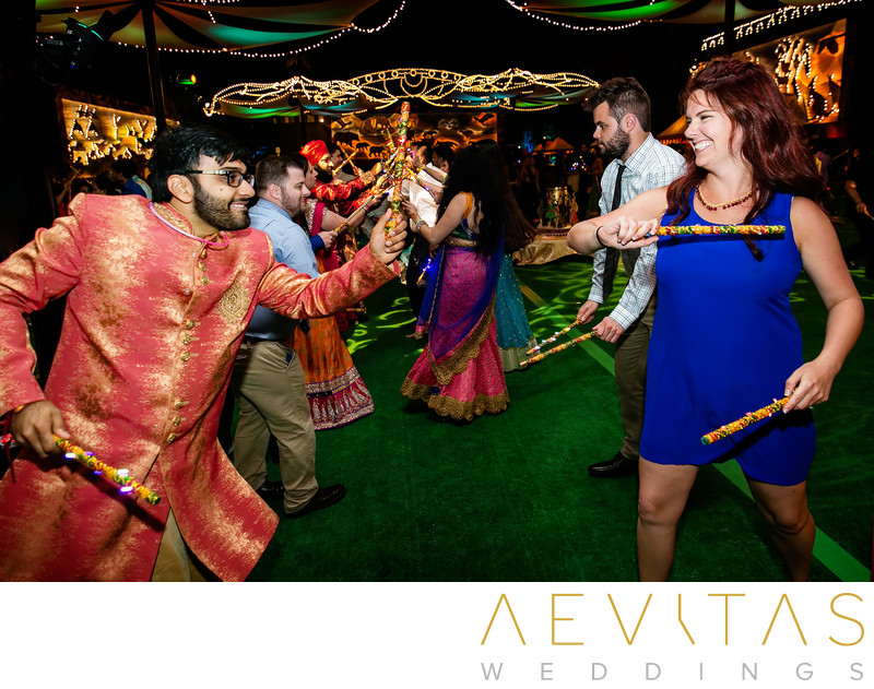 Groom and guest stick dancing at Indian wedding party