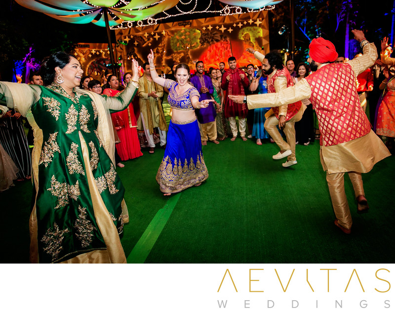 Couples dancing in circle at Indian wedding party