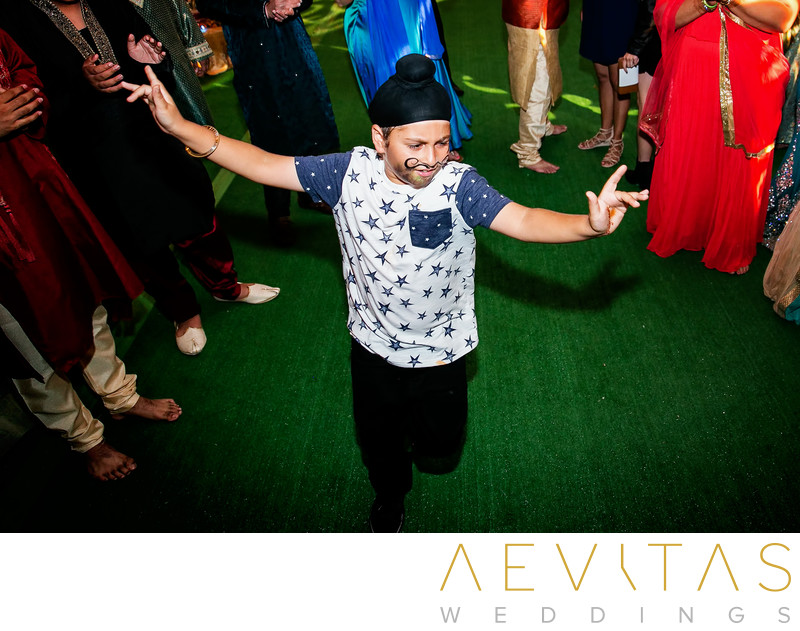 Young wedding guest dancing at Sikh reception party